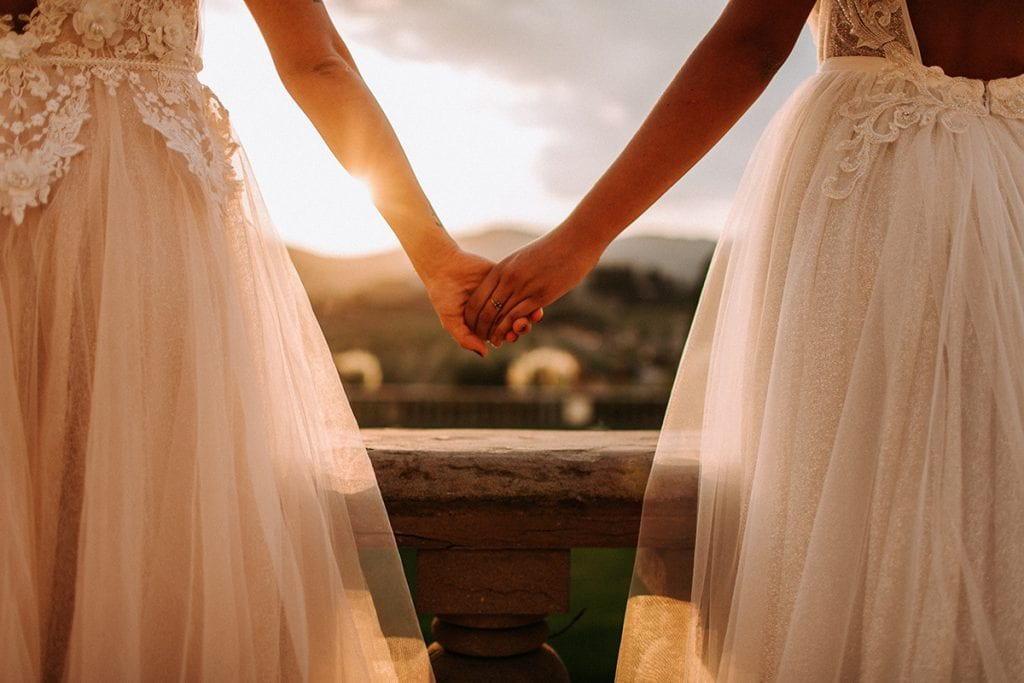 2 brides tuscany wedding holding hands